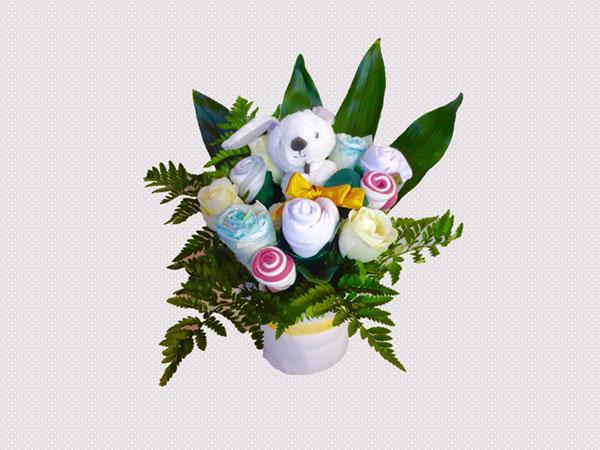 bouquet de naissance avec doudou, bavoir, 2 bodies, 2 paires de chaussettes, couches et fleurs artificielles