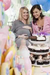 Femme enceinte avec gâteaux et cadeaux pour baby shower entre amis en Guadeloupe